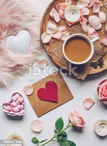 Valentine's Day flat lay: gift card, cup of coffee, rose flowers, candles and candies