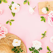 istock Valentines day. Floral frame with roses, straw hat and gift on pastel pink background. Flat lay, top view. 1064039980