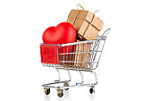 Gift packs and heart shape in shopping cart on white background