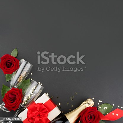 Valentines day composition flat lay top view with gift box rose flowers gift champagne and hearts design element on black background with copy space for text