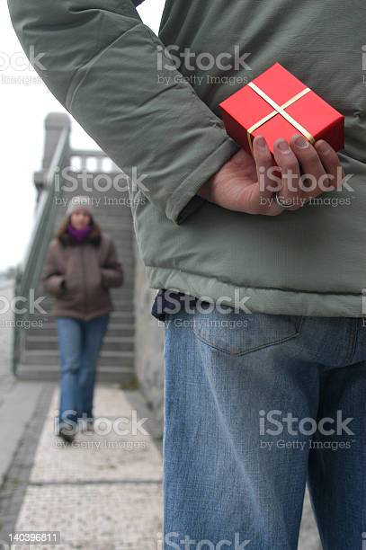 Valentine's Day Gift Valentine's Day Gift. Young man with a red gift box waiting for a girl Adult Stock Photo