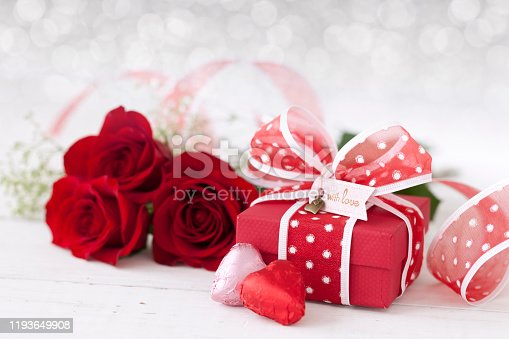 Valentine's Day Gift with Red Roses and Chocolates on a defocused lights background