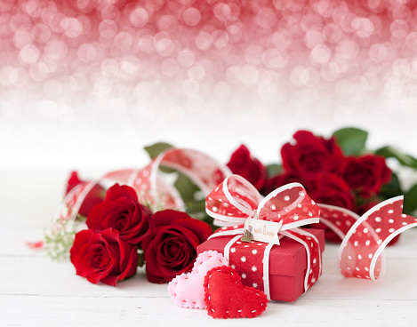 Valentine's Day Gift with Red Roses on a defocused lights background