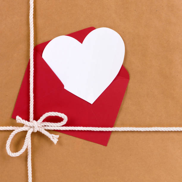 Valentines day gift with white heart shape card, red envelope, brown paper package parcel background stock photo