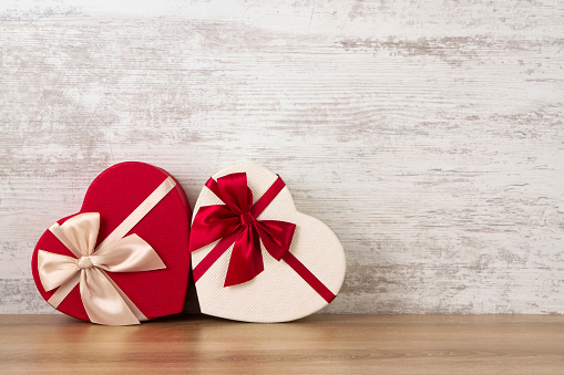 Two contrast coloured gift boxes for holiday on wooden surface.