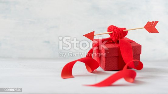 970844120 istock photo Valentines day greeting card, banner, mockup with copy space. Red gift box with thread heart, Cupid's arrow, ribbons on grey background, selective focus. 1096582370