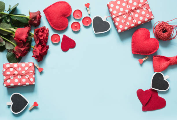 Valentine's day greeting card. Composition with gifts, roses, red hearts on blue surface. Top view. Copy space. stock photo