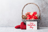 Valentine's day greeting card with gift boxes and knitted hearts in basket. With space for your greetings