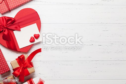 Valentine's day greeting card with heart gift boxes on wooden background. Top view with space for your greetings. Flat lay