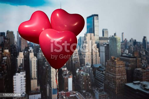 Valentines day in the New York city. man and woman hands holding three red balloons in form of heart over Manhattan and skyscrapers. oncept. America. USA. Aerial view.