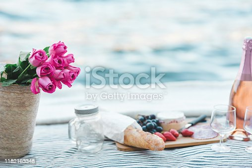 Shot of a romantic picnic laid out next to the water's edge