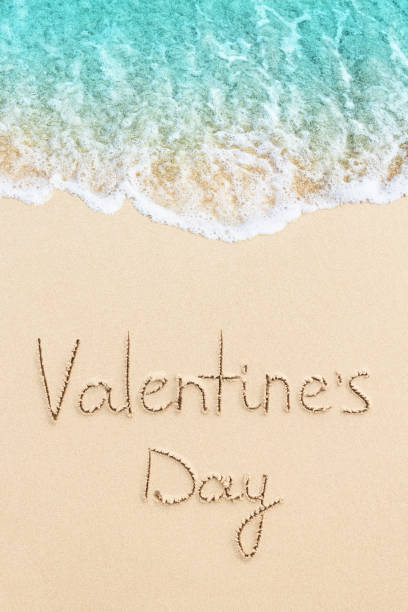 Valentine's Day is written on the sand stock photo