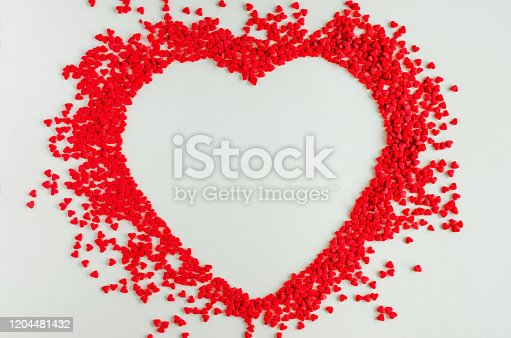 Valentines day love background. Red sugar hearts in the shape of a big heart. Creeting card for Valentines Day. Copy space, top view. Horizontal orientation.