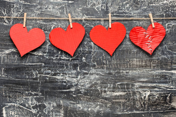 Valentine's Day. One of four hearts are broken Four hearts hanging on rope with copy space on black and white textured background sentimentality stock pictures, royalty-free photos & images