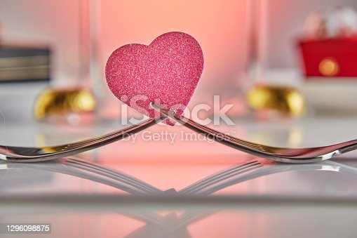 Valentine's Day or romantic birthday dinner with candy hearts, champagne glasses and elegant table setting with reflection.