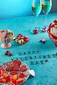 Valentine's day or romantic dinner with candy hearts, glasses of champagne and elegant table setting and Valentine's Day lettering on a light blue background.