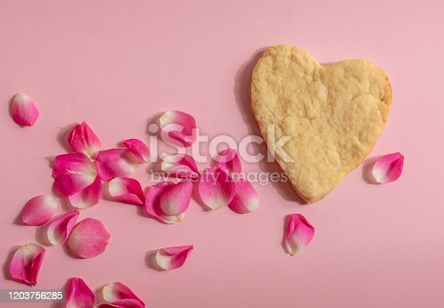 It is a heart cookie on a pink background with rose petals