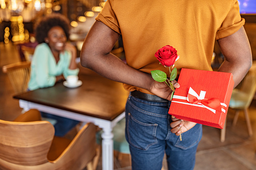 Man hiding red rose behind his back and gift for his smiling girlfriend while sitting in restaurant.