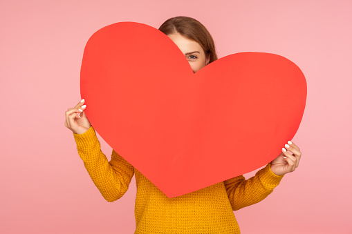 Valentine's day. Portrait of funny girl hiding behind big red heart and looking at camera with playful eyes, holding symbol of love and affection. indoor studio shot isolated on pink background