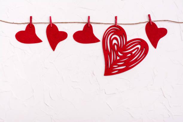 Sevgililer Günü. Farklı boyutlarda keçe kırmızı kalpler beyaz bir arka plan üzerinde bir ip asılı. Dışlama kavramı stok fotoğrafı