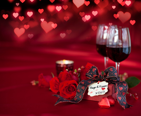Valentine's Day Red Roses and Red Wine with a Gift on a Defocused Lights Background