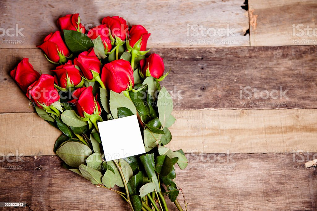 Valentine's Day. Red roses bouquet, blank notecard. Rustic wooden table. stock photo
