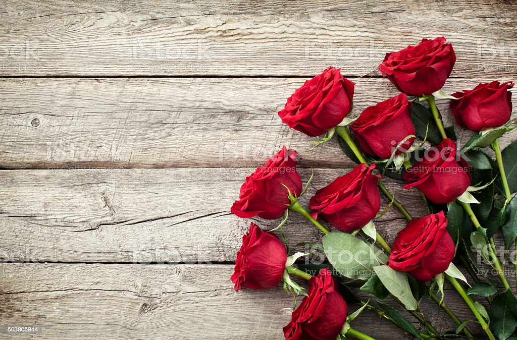 Valentine's day red roses bouquet on old rustic wood background stock photo