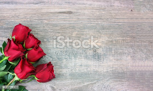 istock Valentine's Day Red Roses Over Wood Background 902728322