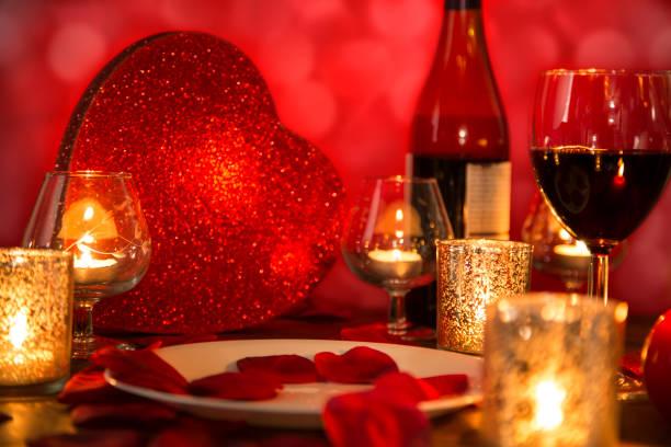 romantisches candle-light dinner zum valentinstag mit herz geschenk und wein. - roten küchentische stock-fotos und bilder