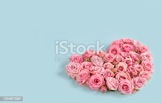 507397624 istock photo Valentine's day romantic greeting card. Composition with a heart of pink roses on a blue background.Mothers day. 8 Marth. Banner for advertising store, website, posters, advertising, coupons. 1204872051