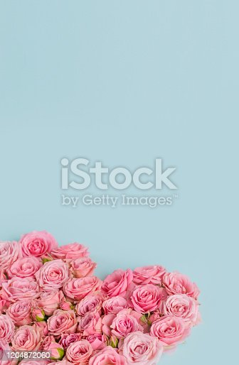 507397624 istock photo Valentine's day romantic greeting card. Composition with a heart of pink roses on a blue background.Mothers day. 8 Marth. Banner for advertising store, website, posters, advertising, coupons.vertical 1204872060