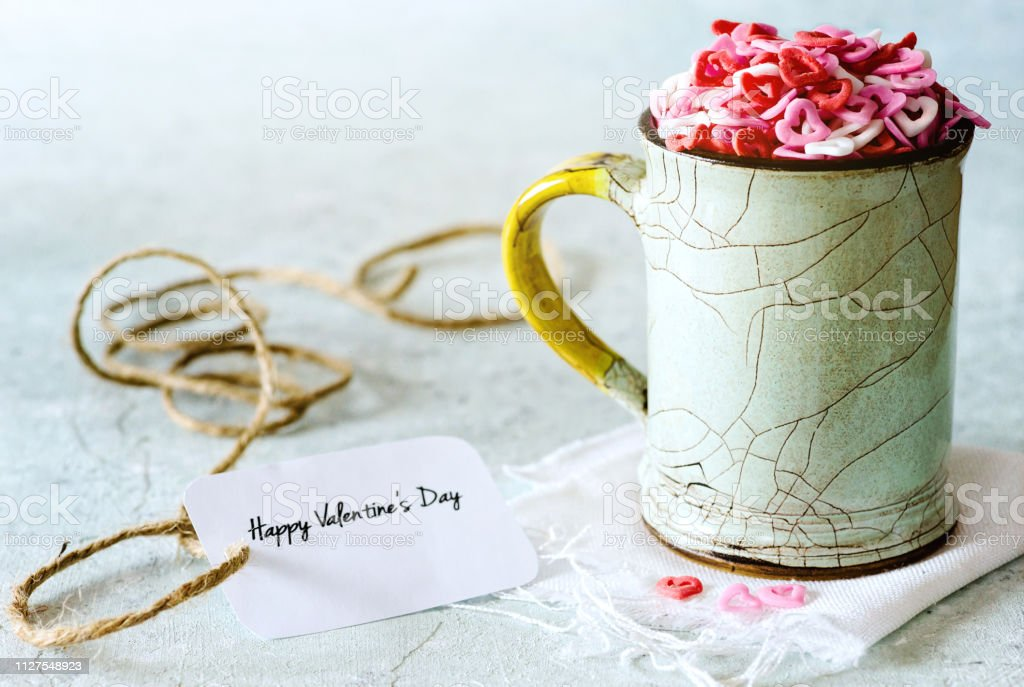 Valentine's day: sugar candies of hearts in a cup on delicate background - foto stock