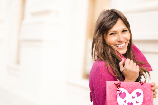 Pretty woman with shopping bag smiling at camera