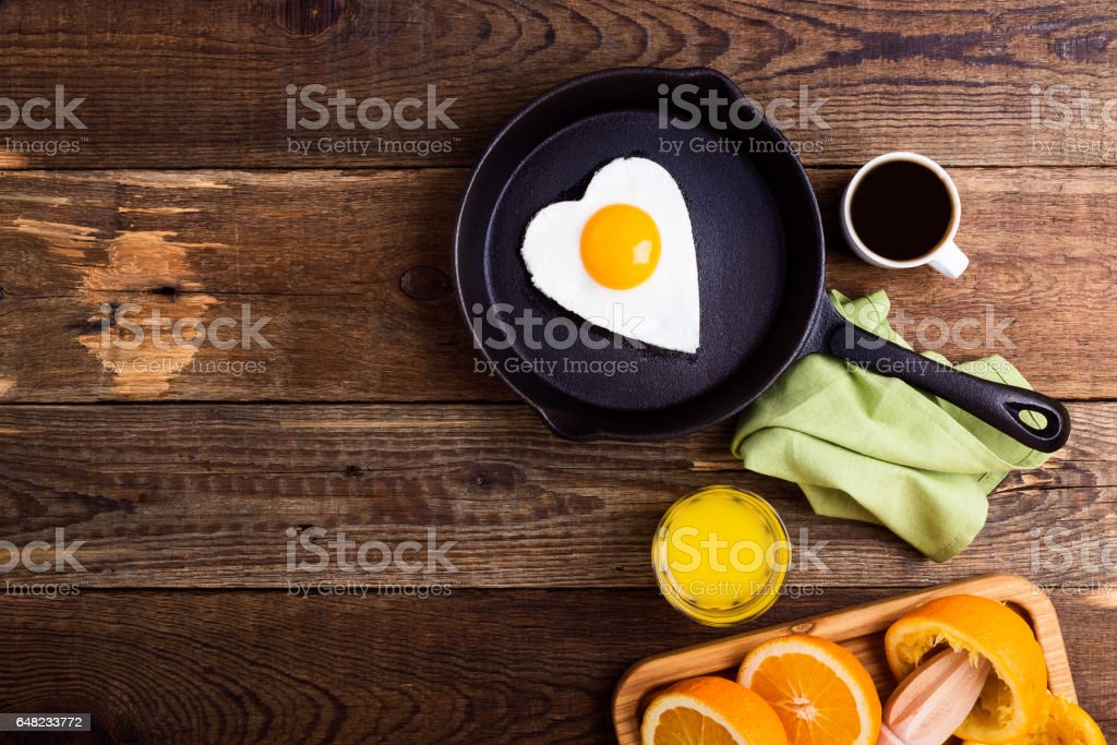 Valentines day table - heart shape fried egg, fresh orange juice and coffee stock photo