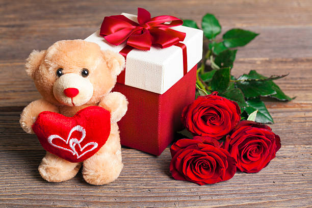 Valentine's Day Teddy Bear Loving with bouquet of Red Roses Valentine's Day Teddy Bear Loving with bouquet of Red Roses and gift box on rustic wooden background. teddy bear stock pictures, royalty-free photos & images