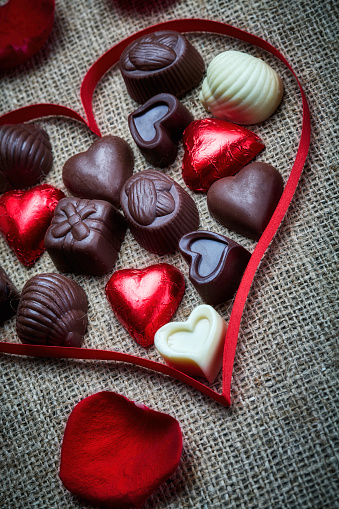 Valentine's Day theme: Chocolate candies in heart shape on a rustic table