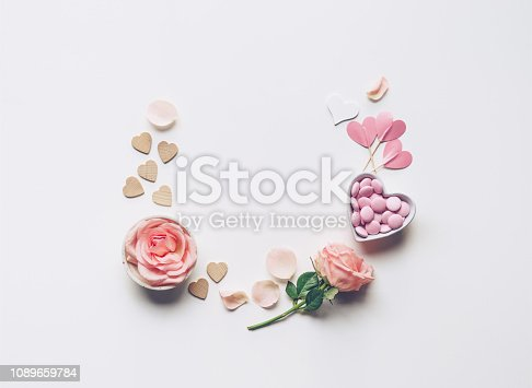 Valentine's Day flat lay: rose flowers and petals, heart shaped candy box on a white background