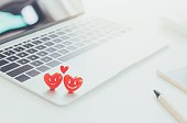 Valentines Day theme,Couple red hearts with smiling face on laptop on white table in office with smartphone and pen.Concept of Online dating website technology.Vintage tone.