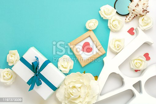 825251738 istock photo Valentines day, wedding, engagement flat lay, top view. Present gift box, ribbon, hearts, rose flowers, Love, blue paper 1197373339