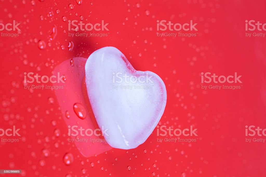 Valentines greeting card with ice heart on red background stock photo
