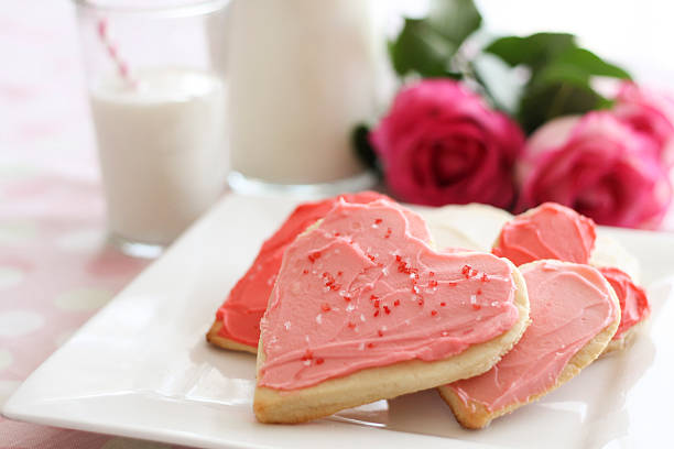 valentine's heart cookies and milk A plate of heart-shaped sugar cookies, a cool glass of milk, and some lovely pink roses await someone special. sugar cookie stock pictures, royalty-free photos & images
