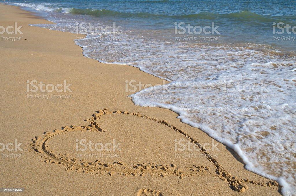 Valentine's love heart on the beach sand stock photo