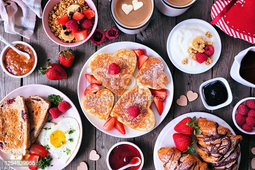 Valentines or Mothers Day brunch table scene. Top view on a dark wood background. Heart shaped pancakes, eggs and an assortment of love themed food.
