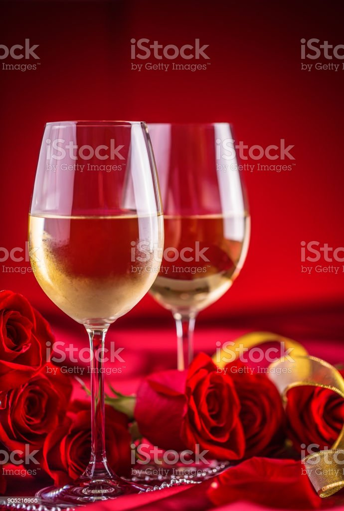 Valentines or wedding concept. Wine cups red roses and romantic setting for two in red. Greeting card for jubilee or aniversary stock photo