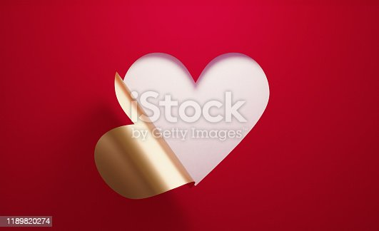 A golden heart shape  folding on red background. Horizontal composition with  copy space.