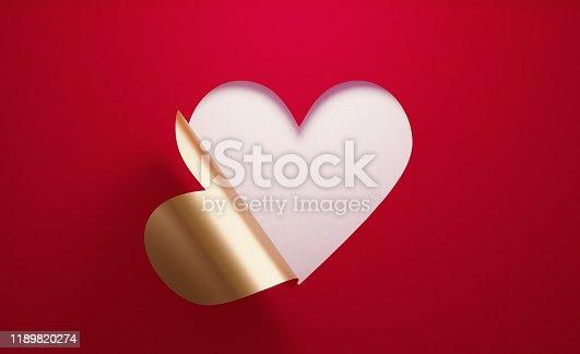 istock Valentıne's Day Concept- A Golden Heart Shape Folding on Red Background 1189820274