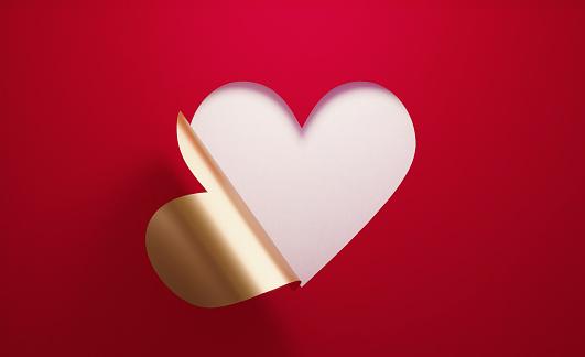 Valentıne's Day Concept- A Golden Heart Shape Folding on Red Background