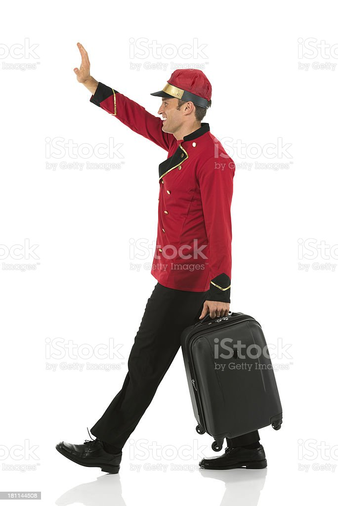 Valet gesturing while walking with a suitcase royalty-free stock photo