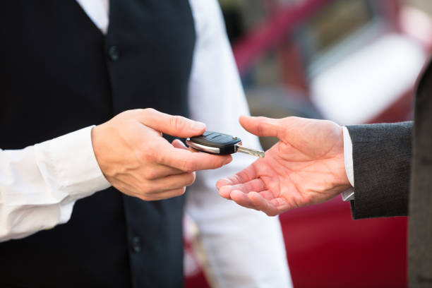 Valet Giving Car Key To Businessperson stock photo