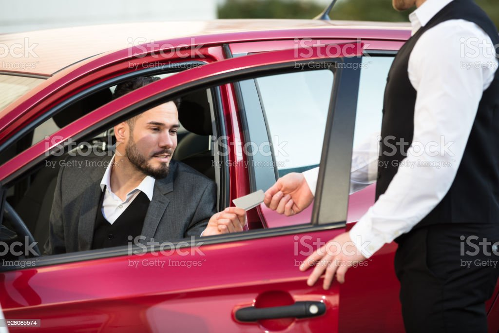Valet Giving Receipt To Businessperson Sitting Inside Car stock photo